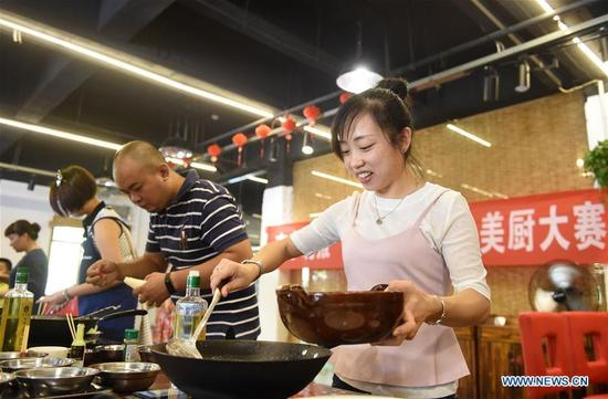 People participate in a cooking contest in Nanning, capital of south China's Guangxi Zhuang Autonomous Region, Oct. 7, 2016, the last day of China's National Day holiday. (Photo/Xinhua)