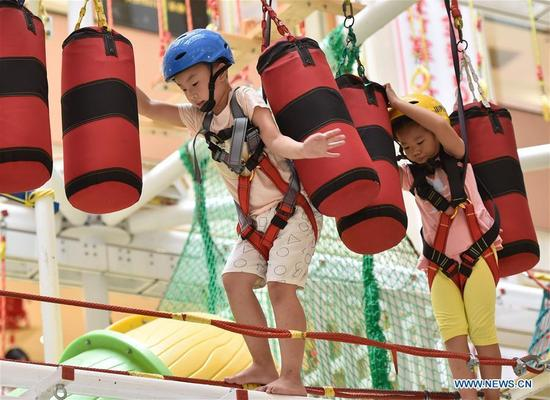 Kids experience an adventure game at a mall in Fuzhou, capital of southeast China's Fujian Province, Oct. 7, 2016, the last day of China's National Day holiday. (Photo/Xinhua)