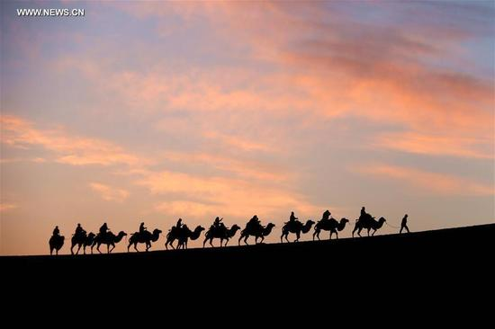 Tourists ride camels at Yueya Spring, a crescent-shaped lake surrounded by deserts, in Dunhuang, northwest China's Gansu province, Oct. 1, 2016. Altogether 593 million people visited tourist attractions around the country and spent 482.2 billion yuan (about 72.3 billion U.S. dollars) during this year's National Day holiday, up 12.8 percent and 14.4 percent respectively year on year, according to the China National Tourism Administration. (Photo/Xinhua)