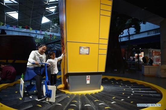 A woman takes her child to try a bike with square wheels at Ningxia Science and Technology Museum in Yinchuan, Ningxia Hui Autonomous Region, Oct. 7, 2016, the last day of China's National Day holiday. (Photo/Xinhua)
