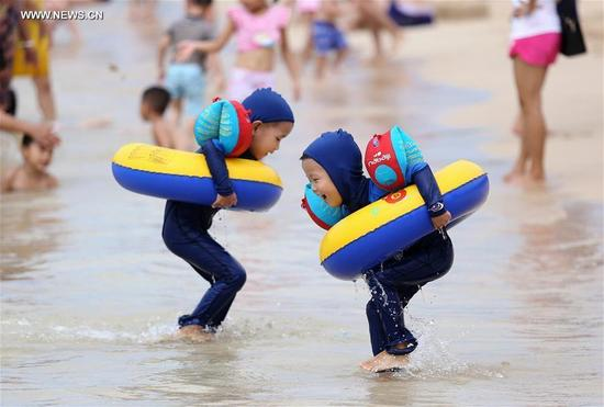 Kids play on the beach in Sanya, south China's Hainan Province, Oct. 2, 2016. Altogether 593 million people visited tourist attractions around the country and spent 482.2 billion yuan (about 72.3 billion U.S. dollars) during this year's National Day holiday, up 12.8 percent and 14.4 percent respectively year on year, according to the China National Tourism Administration. (PhotoXinhua)