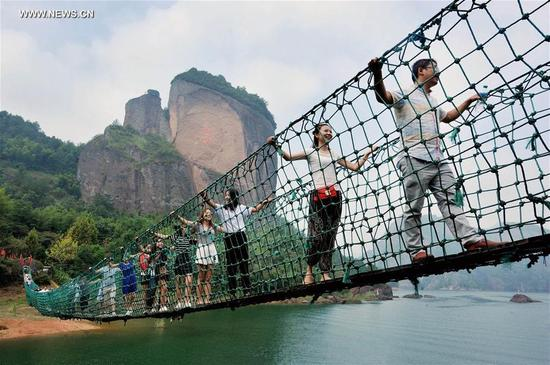 Tourists walk on a rope bridge at Jiuxianhu scenic spot in Shangrao City, east China's Jiangxi Province, Oct. 7, 2016. Altogether 593 million people visited tourist attractions around the country and spent 482.2 billion yuan (about 72.3 billion U.S. dollars) during this year's National Day holiday, up 12.8 percent and 14.4 percent respectively year on year, according to the China National Tourism Administration. (Photo/Xinhua)
