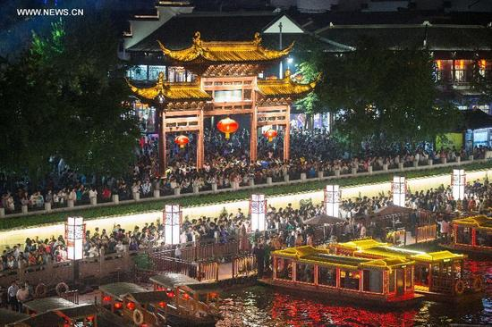 Tourists visit the Nanjing Confucius Temple in Nanjing, capital of east China's Jiangsu Province, Oct. 5, 2016. Altogether 593 million people visited tourist attractions around the country and spent 482.2 billion yuan (about 72.3 billion U.S. dollars) during this year's National Day holiday, up 12.8 percent and 14.4 percent respectively year on year, according to the China National Tourism Administration. (Photo/Xinhua)