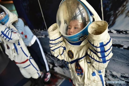A young boy tries on an imitation of spacesuit at Ningxia Science and Technology Museum in Yinchuan, Ningxia Hui Autonomous Region, Oct. 7, 2016, the last day of China's National Day holiday. (Photo/Xinhua)
