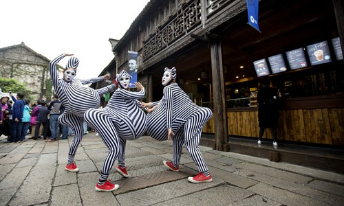 Street performers pose for a photo during the Wuzhen Theatre Festival in October in Wuzhen, Zhejiang Province. Photo: Courtesy of Wuzhen Tourism Co., Ltd