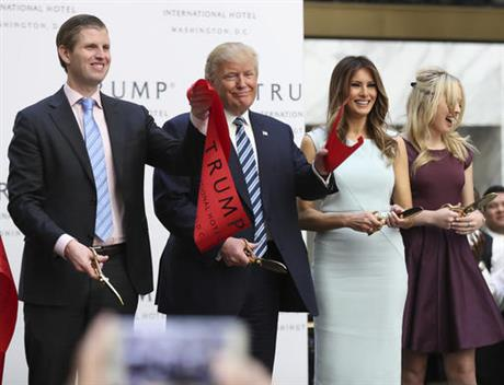 Republican presidential candidate Donald Trump, together with his family, from left, Eric Trump, Melania Trump and Tiffany Trump, waves part of a ribbon after cutting the ribbon during the grand opening of Trump International Hotel in Washington, Wednesday, Oct. 26, 2016.