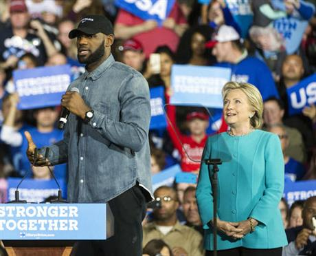 Cleveland Cavaliers star LeBron James speaks as Democratic presidential candidate Hillary Clinton listens during a campaign stop at Cleveland Public Hall in Cleveland, Sunday, Nov. 6, 2016. (AP Photo/Phil Long)