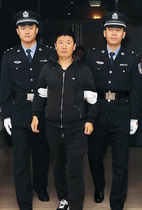 Yan Yongmin, 47, who had been on the run for 15 years, arrives at Beijing international airport from New Zealand on Saturday. The former drug firm chairman initially fled to Australia. — Xinhua