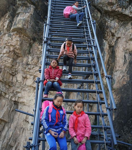 """Atulier village in the Liangshan mountains of Sichuan province had been called """"the Cliff Village"""", for the residents living in the village had to climb on vine ladders if they wanted to go out, even including young students who went to school on the county miles away. The village attracts the public eye as media coverage about the harsh road conditions there went across the country. On November 19, new ladders made of steel were seen in place of the old ones made of vines and woods. Students and parents  started to use the much safer ladders immediately."""