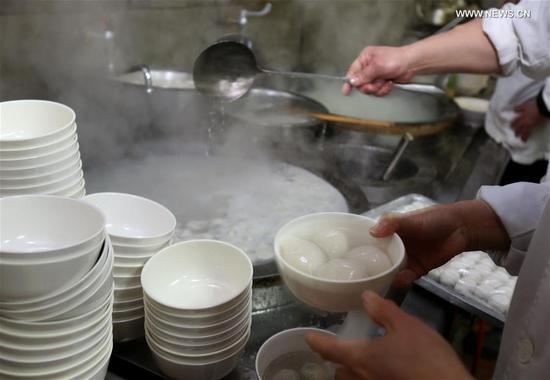 "Cooks boil Tangyuan, a kind of round and sweet dumpling made of glutinous rice flour, at time-honored store named ""Ningbo Dumplings"" in Shanghai, east China, Feb. 9, 2017. As a tradition, Chinese eat Tangyuan to celebrate the Lantern Festival on the 15th day of the Lunar New Year which this year falls on the Feb. 11. About 70,000 sweet dumplings have been sold per day by this store during the past few days. (Xinhua/Liu Ying)"