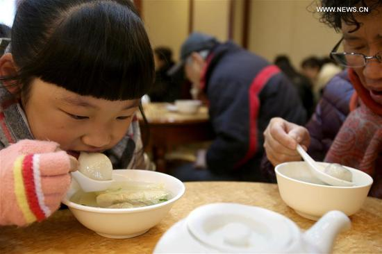 "People eat Tangyuan, a kind of round and sweet dumpling made of glutinous rice flour, at time-honored store named ""Ningbo Dumplings"" in Shanghai, east China, Feb. 9, 2017. As a tradition, Chinese eat Tangyuan to celebrate the Lantern Festival on the 15th day of the Lunar New Year which this year falls on the Feb. 11. About 70,000 sweet dumplings have been sold per day by this store during the past few days. (Xinhua/Liu Ying)"