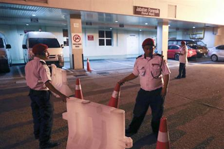 Hospital security personnel block the entrance of the Forensic department at the hospital, in Putrajaya, Malaysia, Tuesday, Feb. 14, 2017. Malaysian police says a unidentified North Korean man died en route to hospital from a Kuala Lumpur airport. (AP Photo/Vincent Thian)