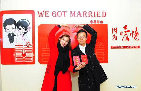A couple holding their marriage certificates pose for photos at a marriage registration center in Wuxi, east China's Jiangsu Province, Feb. 14, 2017. Many couples registered for marriage on Valentine's Day. (Xinhua/Huan Yueliang)