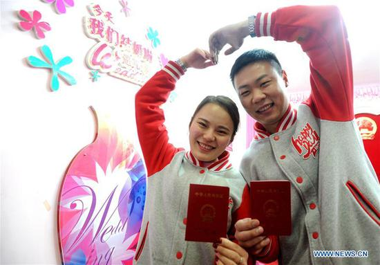 A couple holding their marriage certificates pose for photos at a marriage registration center in Suzhou, east China's Jiangsu Province, Feb. 14, 2017. Many couples registered for marriage on Valentine's Day. (Xinhua/Hang Xingwei)