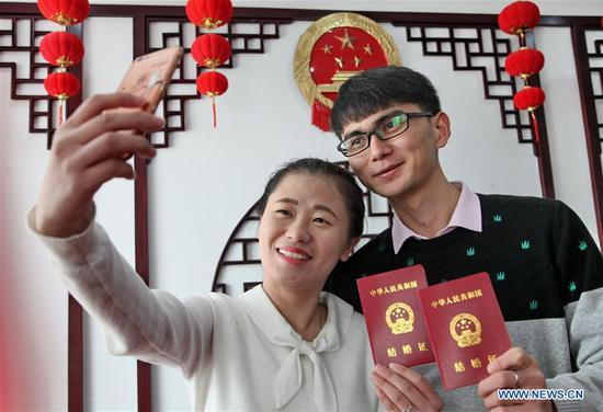 A couple holding their marriage certificates pose for photos at a marriage registration center in Shanghai, east China, Feb. 14, 2017. Many couples registered for marriage on Valentine's Day. (Xinhua/Zhuang Yi)