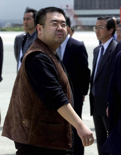 FILE - In this May 4, 2001, file photo, a man believed to be Kim Jong Nam, the eldest son of then North Korean leader Kim Jong Il, looks at a battery of photographers as he exits a police van to board a plane to Beijing at Narita international airport in Narita, northeast of Tokyo. Malaysian officials say a North Korean man has died after suddenly becoming ill at Kuala Lumpur's airport. The district police chief said Tuesday feb. 14, 2017 he could not confirm South Korean media reports that the man was Kim Jong Nam, the older brother of North Korean leader Kim Jong Un. (AP Photo/Shizuo Kambayashi, File)