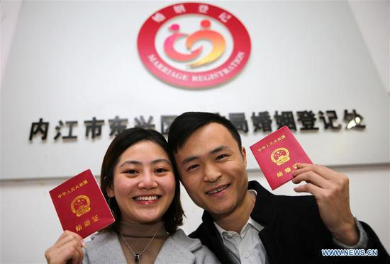 A couple holding their marriage certificates pose for photos at a marriage registration center in Neijiang City, southwest China's Sichuan Province, Feb. 14, 2017. Many couples registered for marriage on Valentine's Day. (Xinhua/Lan Zitao)