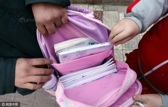 Students of Jinglongchi Primary School in Xi'an, capital city of Shaanxi province were companied by parents to the school on February 13. Many of the pupils or their parents carried a heavy schoolbag, some even weighs over 6 kg. The bags were full of textbooks.