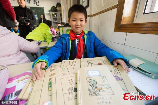 Photos taken on Feb. 15, 2017 show cartoons painted by a sports teacher on a self-made book cover for his son, a third grader, in Hangzhou City, the capital city of East China's Zhejiang Province. The father wanted to make the book cover interesting so he copied cartoons of famous Chinese artist Feng Zikai, a favorite author of his son. (Photo/CFP)