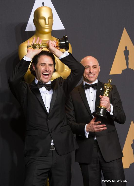 Director Alan Barillaro and producer Marc Sondheimer pose after winning the Best Animated Short Film award for