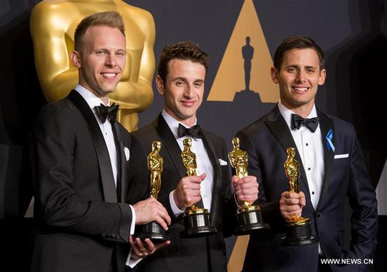 (L-R) Songwriters Justin Paul, Justin Hurwitz and Benj Pasek pose after winning the Best Original Song award for