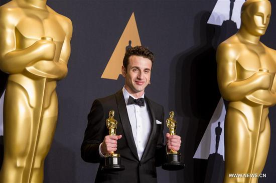 Justin Hurwitz poses after winning the Best Original Score award and the Best Original Song award for