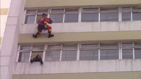The firefighters dispersed the crowd and prepared an air cushion on the ground. Then they decided to have one soldier wired down from the tenth floor and push the woman back into the window.
