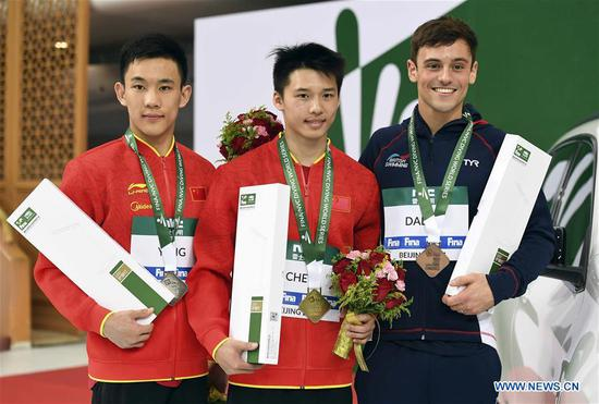 Gold medalist Chen Aisen (C) of China, his teammate silver medalist Yang Hao (L) and bronze medalist Thomas Daley of Britain react during the awarding ceremony for men's 10m platform of the FINA Diving World Series 2017 in Beijing, capital of China, March 5, 2017. (Xinhua/Tao Xiyi)