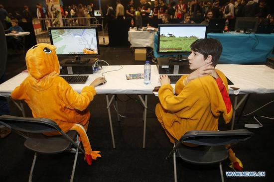 Two boys wearing costumes play computer games at Made in Asia animation and cartoon products fair in Brussels, Belgium, on March 5, 2017. (Xinhua/Ye Pingfan) 136105071_14887558309551n