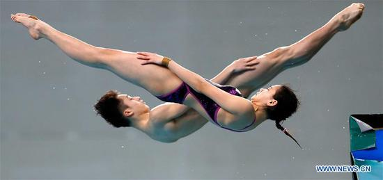 Lian Jie (Front)/Lian Junjie of China compete during the mixed 10m platform final of the FINA Diving World Series 2017 in Beijing, capital of China, March 5, 2017. Lian Jie/Lian Junjie claimed the title of the event with a total of 329.28 points. (Xinhua/Wang Lili)