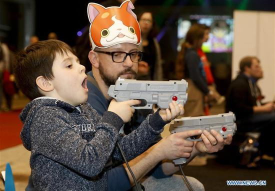 A boy and his father play a shooting video game at Made in Asia animation and cartoon products fair in Brussels, Belgium, on March 5, 2017. (Xinhua/Ye Pingfan)