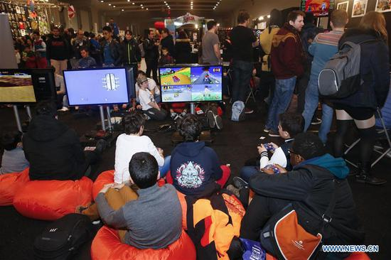 People play video games at Made in Asia animation and cartoon products fair in Brussels, Belgium, on March 5, 2017. (Xinhua/Ye Pingfan)
