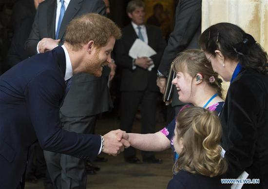 Prince Harry (L, Front) shakes hands with one of the flower girls after attending the Commonwealth Day celebrations service at Westminster Abbey in London, Britain, on March 13, 2017. (Xinhua)