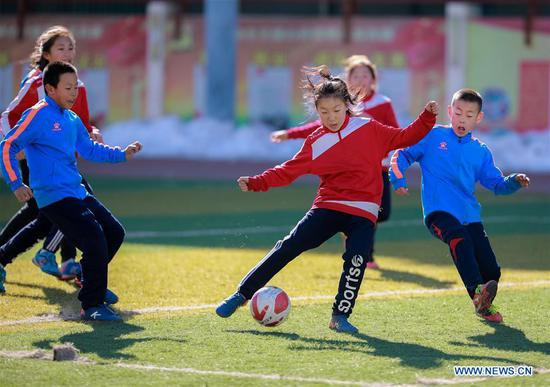 Members of girl's soccer team in a primary school compete with boys during a soccer game in Yuquan District of Hohhot, capital of north China's Inner Mongolia Autonomous Region, March 15, 2017. (Xinhua/Ding Genhou)