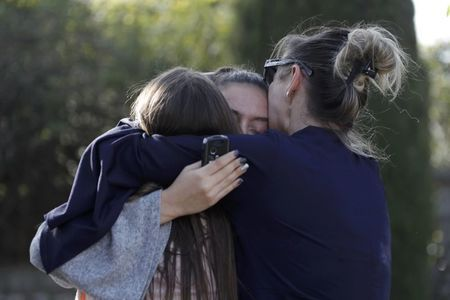 People embrace near the Tocqueville high school after a shooting has taken place in Grasse, southern France, March 16, 2017. REUTERS/Eric Gaillard