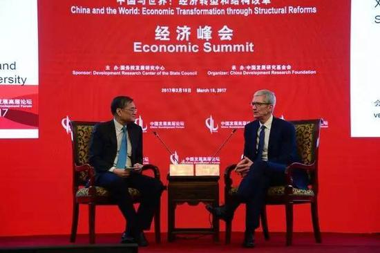 Apple CEO Tim Cook (R) talked with Qian Yingyi, head of the School of Economics and Management in Tsinghua University at the summit.