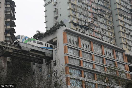 The No.2 light-rail train drives through a building in Liziba Station, Chongqing Municipality.