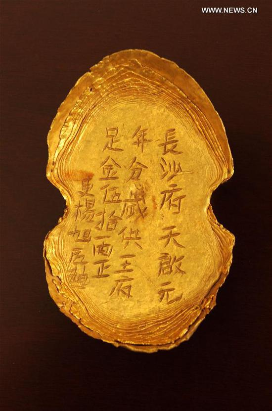 Photo taken on March 17, 2017 shows a golden ingot unearthed at Pengshan District in Meishan City, southwest China's Sichuan Province. More than 10,000 gold and silver items that sank to the bottom of a river in Sichuan Province over 300 years ago have been recovered, archeologists said Monday. The items included a large amount of gold, silver and bronze coins and jewelry as well as iron weapons such as swords, knifes and spears. (Xinhua/Chen Xie)