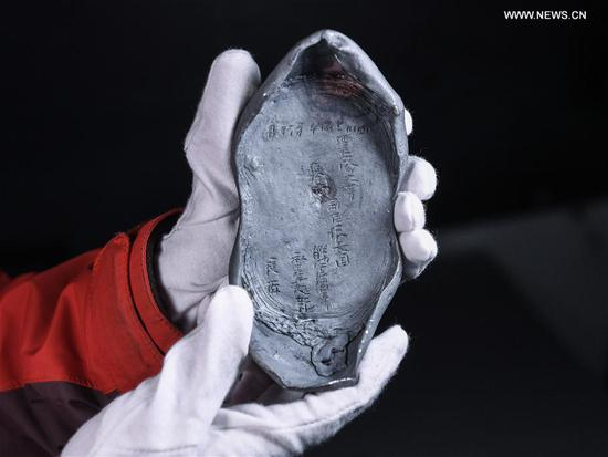 Photo taken on March 19, 2017 shows a silver ingot unearthed during an archaeological excavation in Pengshan District under Meishan City, southwest China's Sichuan Province. More than 10,000 gold and silver items that sank to the bottom of a river in Sichuan Province over 300 years ago have been recovered, archeologists said Monday. The items included a large amount of gold, silver and bronze coins and jewelry as well as iron weapons such as swords, knifes and spears. (Xinhua/Li He)