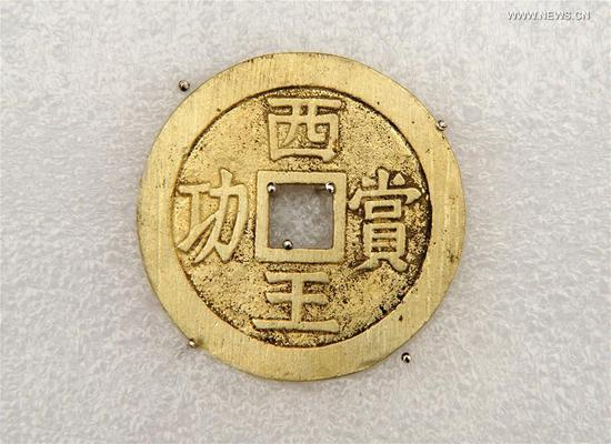 Photo taken on March 17, 2017 shows a gold coin unearthed during an archaeological excavation at Pengshan District in Meishan City, southwest China's Sichuan Province. More than 10,000 gold and silver items that sank to the bottom of a river in Sichuan Province over 300 years ago have been recovered, archeologists said Monday. The items included a large amount of gold, silver and bronze coins and jewelry as well as iron weapons such as swords, knifes and spears. (Xinhua/Chen Xie)
