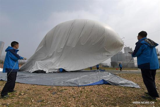 Staff members inflate a captive balloon at a testing ground in Liu'an, east China's Anhui Province, March 29, 2017. The captive balloon is an air platform carrying various devices, such as warning radar, video surveillance equipment, fog detection devices, communication relay devices and imaging equipment. The balloon is expected to play a role in precaution and detection, environmental surveillance, security and protection monitoring. (Xinhua/Guo Chen)