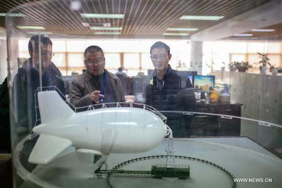 Designers discuss details in front of a captive balloon model at the 38th Research Institute of China Electronics Technology Group Corporation in Hefei, capital of east China's Anhui Province, March 28, 2017. The captive balloon is an air platform carrying various devices, such as warning radar, video surveillance equipment, fog detection devices, communication relay devices and imaging equipment. The balloon is expected to play a role in precaution and detection, environmental surveillance, security and protection monitoring. (Xinhua/Cheng Tingting)
