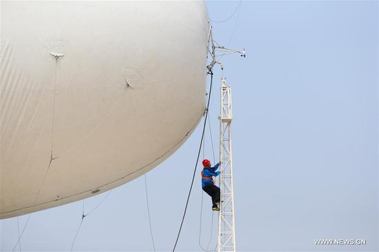 A staff member exaimines a captive balloon on a ladder at a testing ground in Liu'an, east China's Anhui Province, March 29, 2017. The captive balloon is an air platform carrying various devices, such as warning radar, video surveillance equipment, fog detection devices, communication relay devices and imaging equipment. The balloon is expected to play a role in precaution and detection, environmental surveillance, security and protection monitoring. (Xinhua/Cheng Tingting)