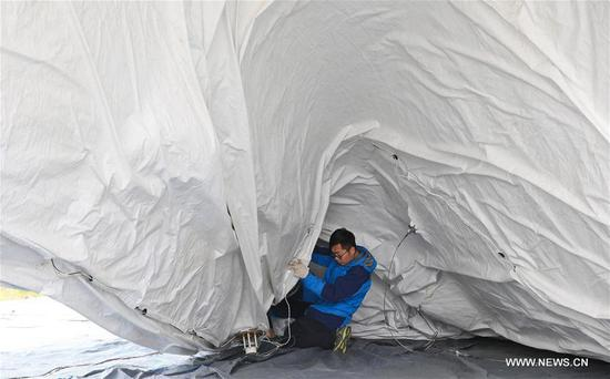 A staff member works under a captive balloon at a testing ground in Liu'an, east China's Anhui Province, March 29, 2017. The captive balloon is an air platform carrying various devices, such as warning radar, video surveillance equipment, fog detection devices, communication relay devices and imaging equipment. The balloon is expected to play a role in precaution and detection, environmental surveillance, security and protection monitoring.(Xinhua/Cheng Tingting)