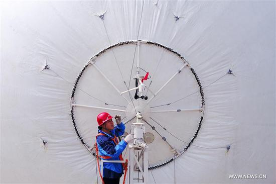 A staff member examines a captive balloon at a testing ground in Liu'an, east China's Anhui Province, March 29, 2017. The captive balloon is an air platform carrying various devices, such as warning radar, video surveillance equipment, fog detection devices, communication relay devices and imaging equipment. The balloon is expected to play a role in precaution and detection, environmental surveillance, security and protection monitoring. (Xinhua/Meng Dingbo)