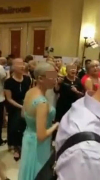 Photo screen shows a bunch of bald women having party in a hotel.