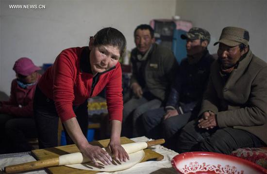 A woman makes food for herdsmen on Bayan Bulag grassland in Hejing County, northwest China's Xinjiang Uygur Autonomous Region, April 6, 2017. In April, Bayan Bulag grassland enters into its busiest season for sheep breeding. (Xinhua/Jiang Wenyao)