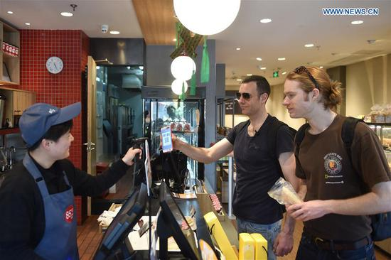 Tim Clancy (C), an Australian who has lived in Hangzhou for six years with his Chinese wife, takes his American friend to buy coffee and bread through mobile payment in Hangzhou, capital of east China's Zhejiang Province, April 14, 2017. Tim took his American friend to make a cash-free travel for one day in Hangzhou, with mobile phones being used to pay all of their costs. Dubbed the world's largest mobile payment city, more than 98 percent of Hangzhou's taxis, over 95 percent of supermarkets and convenience stores, and more than 50 percent of restaurants in Hangzhou have access to mobile payment services. With smartphones, tourists in Hangzhou can use mobile payment service when shopping, dining, or calling a cab. (Xinhua/Huang Zongzhi)