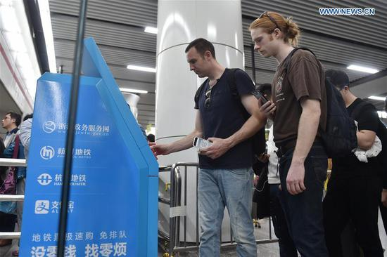 Tim Clancy (L), an Australian who has lived in Hangzhou for six years with his Chinese wife, takes his American friend to pay for subway tickets through mobile payment in Hangzhou, capital of east China's Zhejiang Province, April 14, 2017. Tim took his American friend to make a cash-free travel for one day in Hangzhou, with mobile phones being used to pay all of their costs. Dubbed the world's largest mobile payment city, more than 98 percent of Hangzhou's taxis, over 95 percent of supermarkets and convenience stores, and more than 50 percent of restaurants in Hangzhou have access to mobile payment services. With smartphones, tourists in Hangzhou can use mobile payment service when shopping, dining, or calling a cab. (Xinhua/Huang Zongzhi)