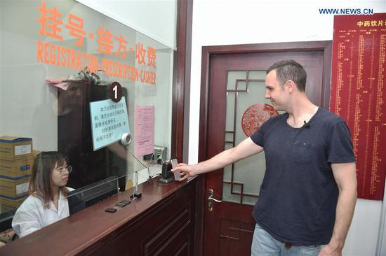 Tim Clancy, an Australian who has lived in Hangzhou for six years with his Chinese wife, registers through mobile payment at a Chinese medicine clinic in Hangzhou, capital of east China's Zhejiang Province, April 14, 2017. Tim took his American friend to make a cash-free travel for one day in Hangzhou, with mobile phones being used to pay all of their costs. Dubbed the world's largest mobile payment city, more than 98 percent of Hangzhou's taxis, over 95 percent of supermarkets and convenience stores, and more than 50 percent of restaurants in Hangzhou have access to mobile payment services. With smartphones, tourists in Hangzhou can use mobile payment service when shopping, dining, or calling a cab. (Xinhua/Huang Zongzhi)